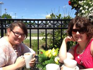Lauren and Chantal enjoying hot beverages on a patio after mass.